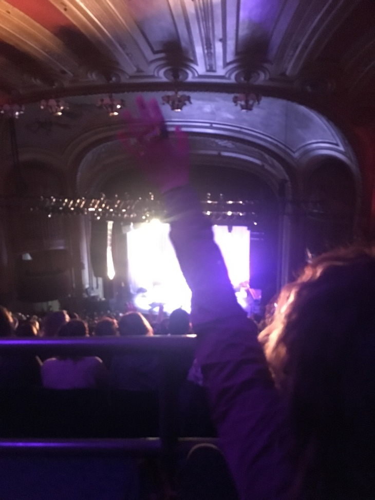 woman with left arm up watching a concert