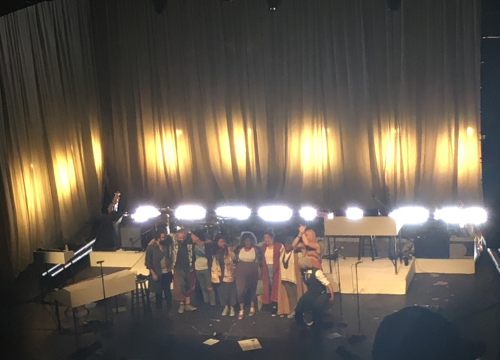 nine people standing on stage facing audience