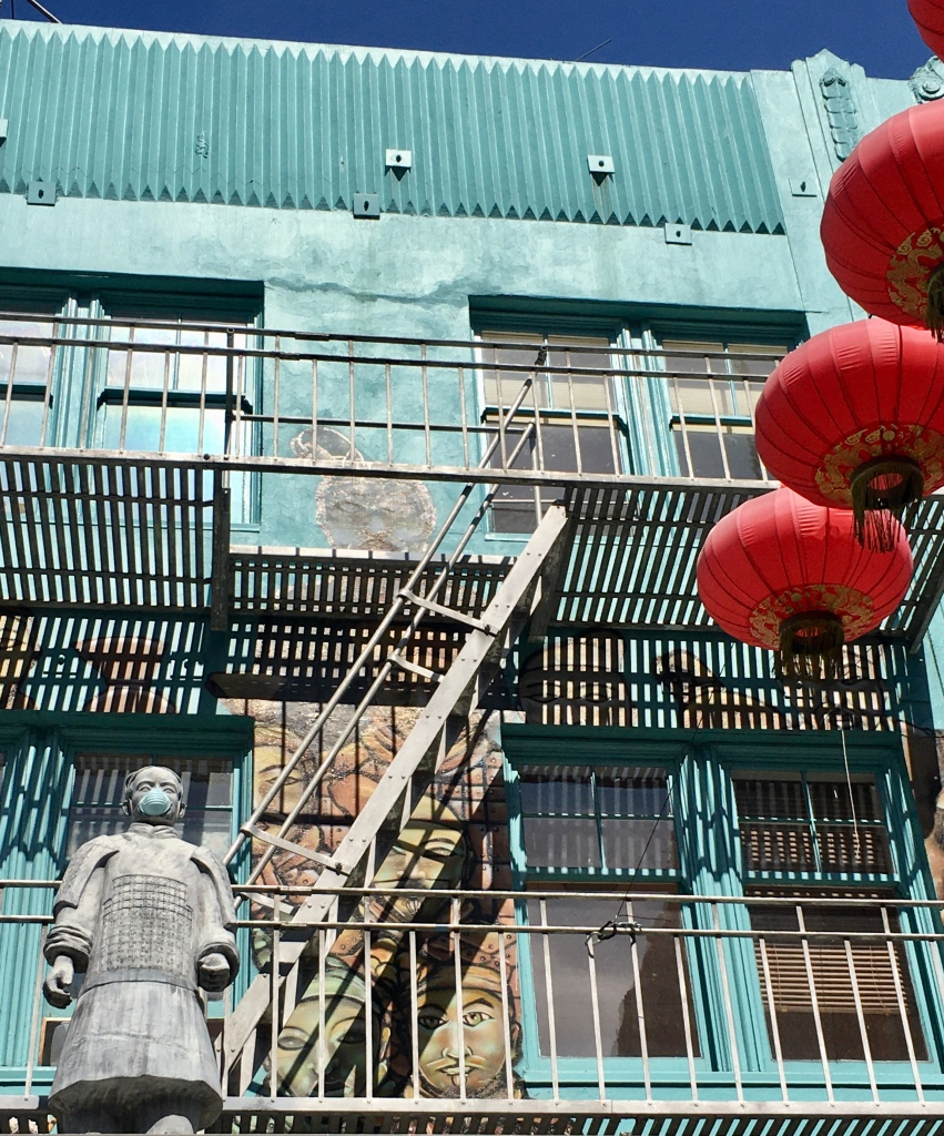 Red lanterns and statue wearing face mask